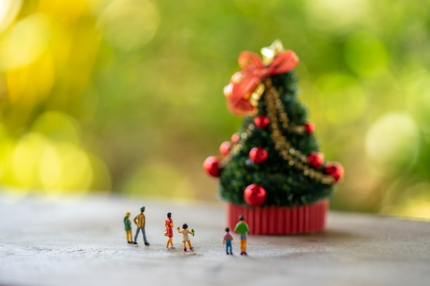 Family miniature people standing on christmas tree celebrate christmas