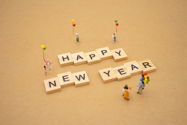 Family miniature people standing with wood word happy new year