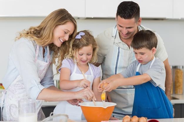 卵を混ぜてクッキーを焼く家族