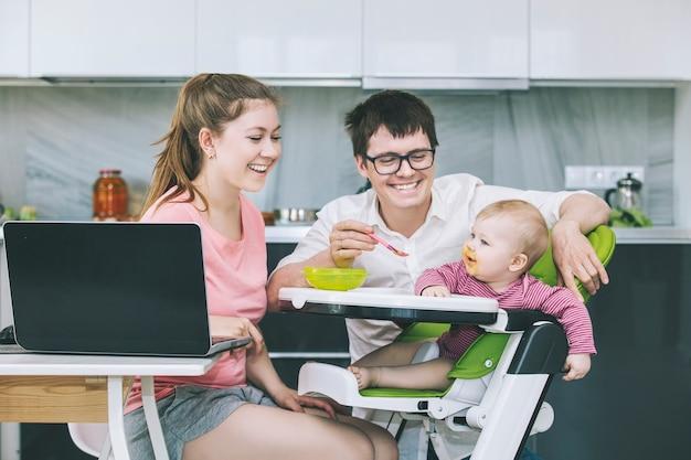 家族のお母さんとお父さんがキッチンで赤ちゃんに餌をやる