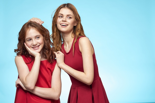家族のお母さんと娘は赤いドレスを抱きしめますコミュニケーション感情青い背景
