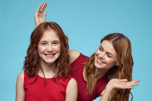 家族のお母さんと娘が赤いドレスのコミュニケーションの感情を抱きしめます