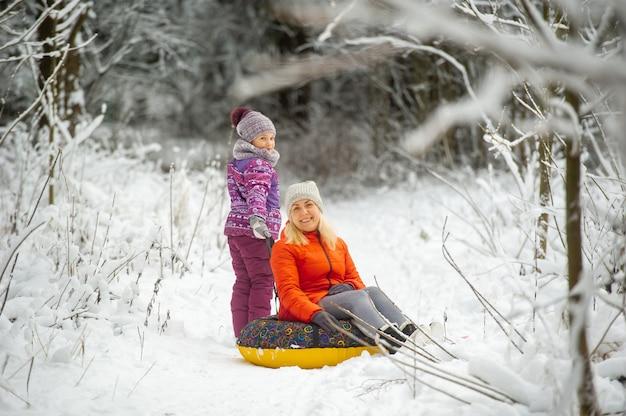 雪に覆われた森の中を歩く膨脹可能な円を持つ冬の家族の母と娘