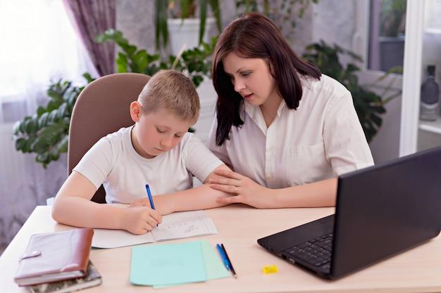 Семья мама и сын делают домашнее задание в комнате на ноутбуке. дистанционное обучение