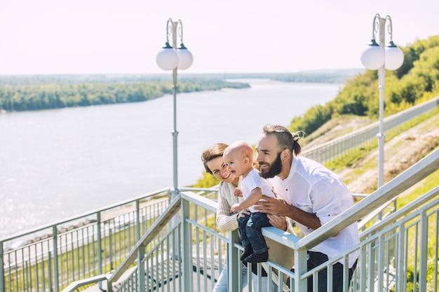 Семья мама, папа и ребенок счастливы вместе с улыбками в парке, гуляя по набережной в летнем портрете