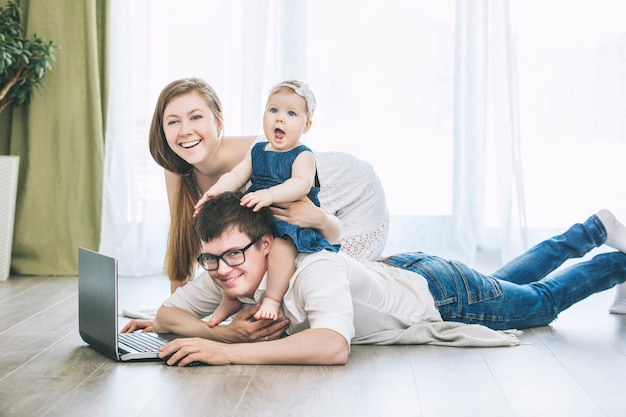 Семья мама, папа и дочь с ноутбуком вместе дома счастливы и красивы