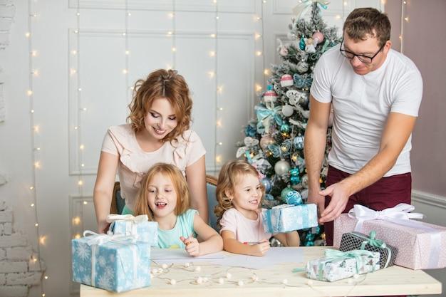 가족 엄마 아빠와 크리스마스 인테리어에 선물을 가진 어린 소녀들은 산타에게 편지를 씁니다.