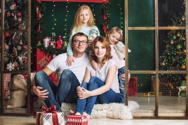 가족 엄마 아빠와 아이들이 크리스마스 인테리어 집에서 함께 행복한 선물을 가지고 있는 어린 소녀들