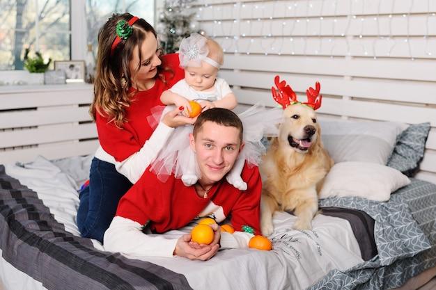 Семья-мама, папа и дочка в рождественских свитерах