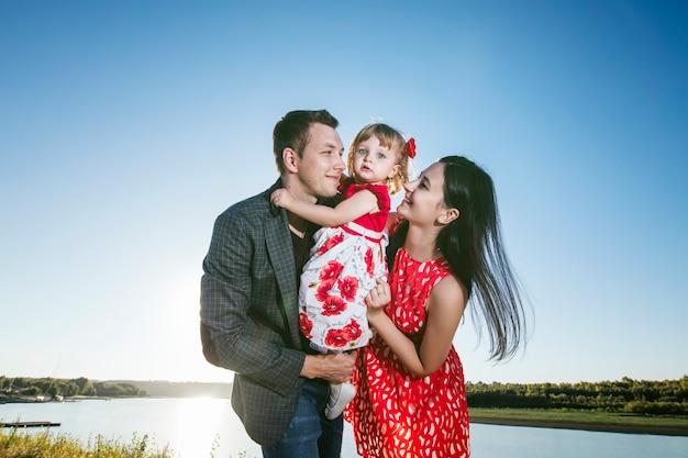 家族、お母さん、お父さんが娘を抱いて幸せで美しい夕日を桟橋で散歩