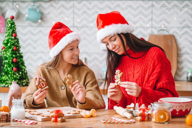 Family of mom and daughter cooking christmas cookies on the kitchen