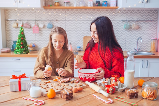 Family of mom and daughter prepare christmas cookies on the kitchen