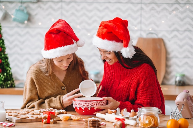 Family of mom and daughter in santa hat prepare christmas cookies on the kitchen