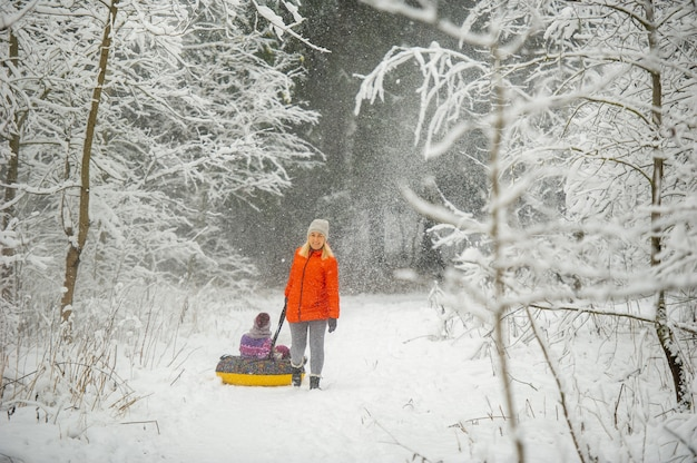 Family mom and daughter in winter with an inflatable circle walk through the snow-covered forest.
