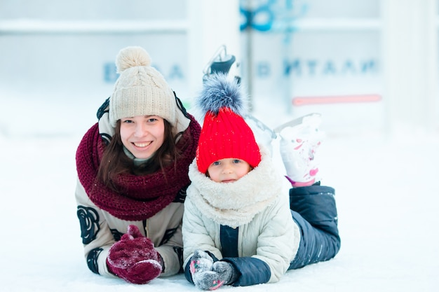 Family of mom and kid lying on ice-rink after fall