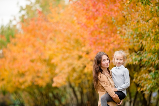 Family of mom and kid outdoors in autumn day