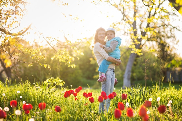 Семья мама с дочерью женщина с ребенком весной стоят и обнимаются на поляне с зеленой травой и тюльпанами на закате