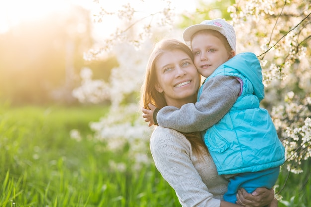Семья мама с дочерью женщина с ребенком весной стоят и обнимаются под цветущим деревом