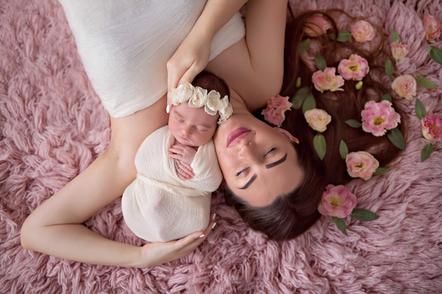 Family, mom with flowers in her hair and a newborn girl lie on the bed. view from above.