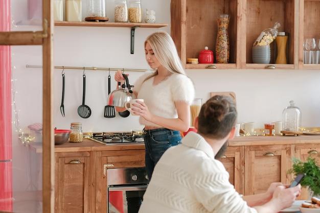 Семейное утро. красивая блондинка заваривает чай для своего мужа на современной кухне.