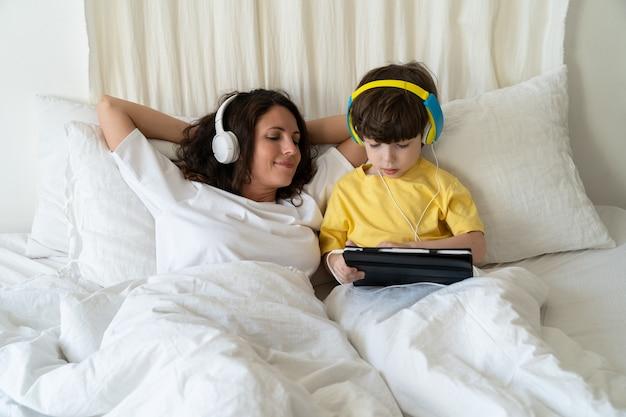 헤드폰을 끼고 침실에 있는 가족의 아침 엄마는 태블릿 컴퓨터에서 어린 아들이 게임을 하는 모습을 봅니다.