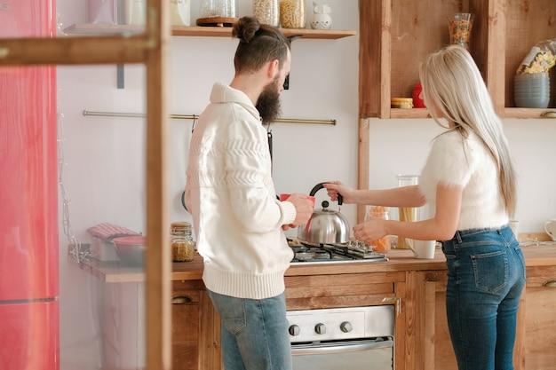 Семейный утренний распорядок. пара заваривает чай на современной кухне с деревянной мебелью.