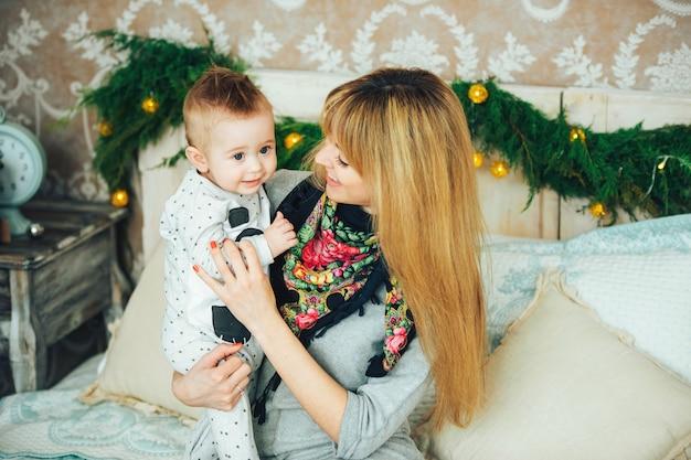 Семья матери и маленького сына, играющего дома на рождественские каникулы. оба улыбаются. концепция зимнего отдыха. домашний интерьер, концепция рождественских праздников.
