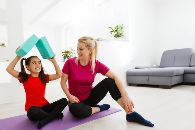 家族の母と子の娘は、自宅でフィットネス、ヨガ、運動に従事しています