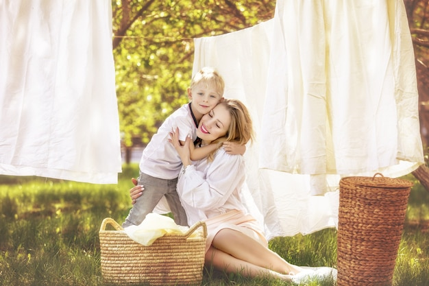 Семья, мать и сын, красивые и счастливые вместе вешают чистое белье в саду