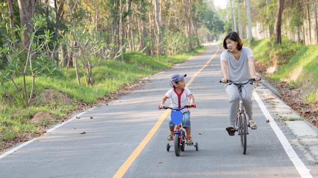 家族。公園に乗っている母と息子