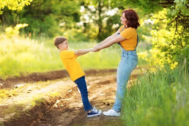 Семья: мама и сын гуляют, держатся за руки, играют летом
