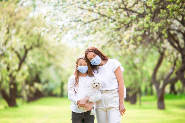Family of mother and daughter in blooming cherry garden in masks with a puppy
