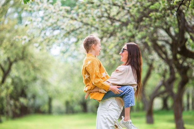 Family of mother and daughter in blooming cherry garden