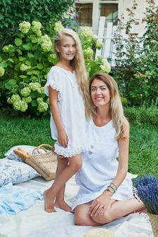 Family mother and daughter in the garden in the summer on a picnic rest