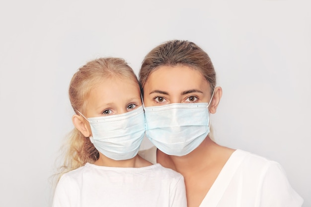 Family mother and daughter in medical masks together on an isolated background
