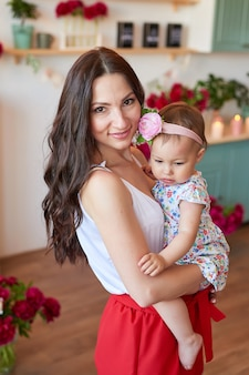 Family mother and daughter with peonies flowers in kitchen at home. happy mother and baby daughter. happy family.