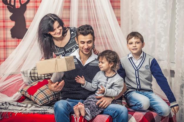 家族の母親の父と子供たちはあなたの家の冬の装飾でお互いに贈り物をします
