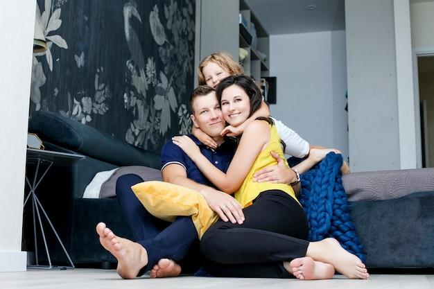 Семья мать, отец и дочь счастливы и красивы с улыбками дома вместе в спальне на полу с подушками
