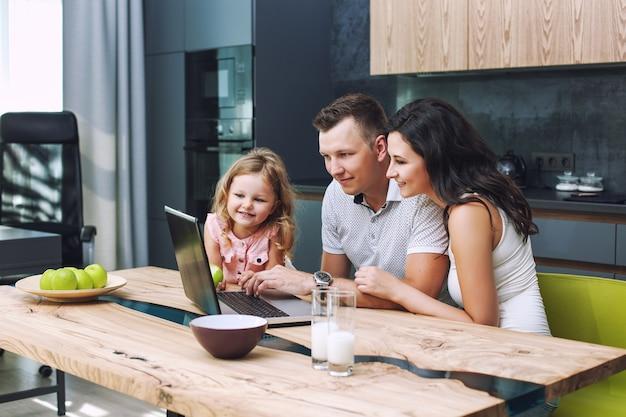 Семья мать, отец и дочь счастливы и красивы с улыбками дома вместе на кухне с ноутбуком