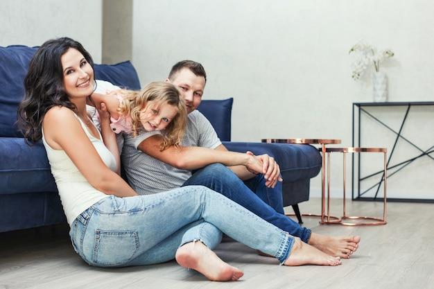 Семья мать, отец и дочь счастливы и красивые с улыбками портрет дома вместе