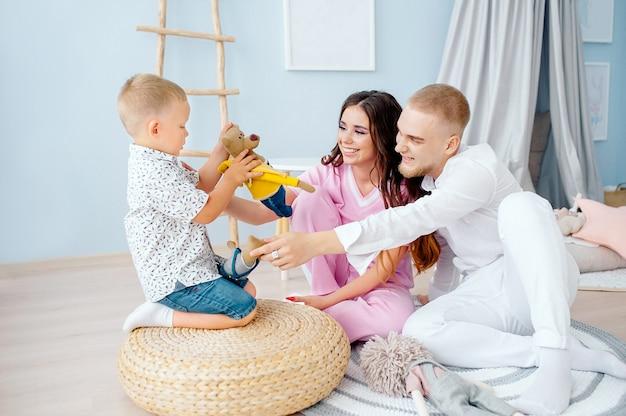 家族の母親の父親と幼い息子が子供の明るいプレイルームで一緒に遊ぶ