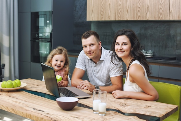 Family mother, father and daughter happy and beautiful with smiles at home together in the kitchen with laptop