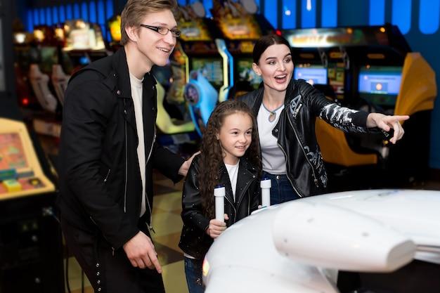 Семья, мать, отец, дочь, играют в аркадные игры на компьютерных машинах в парке развлечений