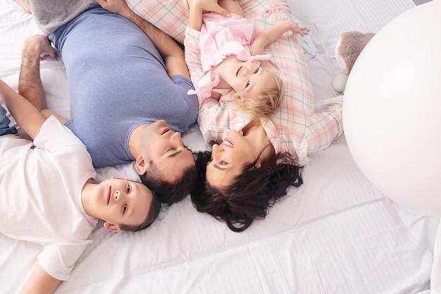 家族の母、父、息子と小さな娘が一緒にベッドの上面図に横たわって幸せ