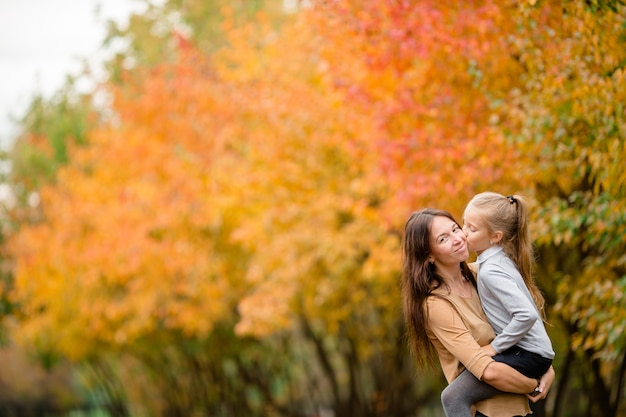 Family of mother and kid outdoors in park at autumn day