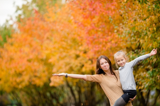 Family of mother and little kid outdoors in park at autumn day