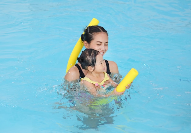 Family of mother teaching kid girl in swimming pool with noodle foam