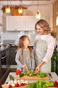 Семья мать с дочерью готовят вместе, счастливая девушка рада помочь матери готовить салат, смешивая свежие овощи