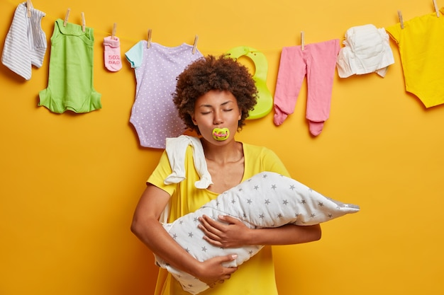 家族、母性、子育ての概念。母は小さな赤ちゃんを手に持って、お母さんになる瞬間を楽しんで、乳首を口に入れて目を閉じてポーズをとり、後ろに新生児の服を着たロープ、黄色い壁