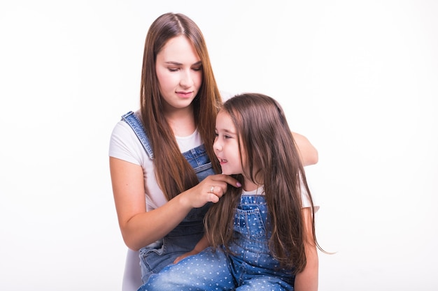 Family, motherhood and parent concept - mother combing her little daughter's hair isolated on white wall.